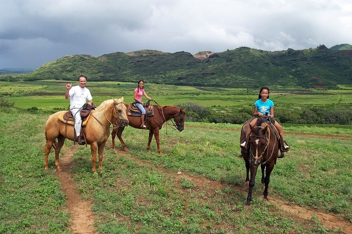 dad with daughters on horses - hawaiian greeting