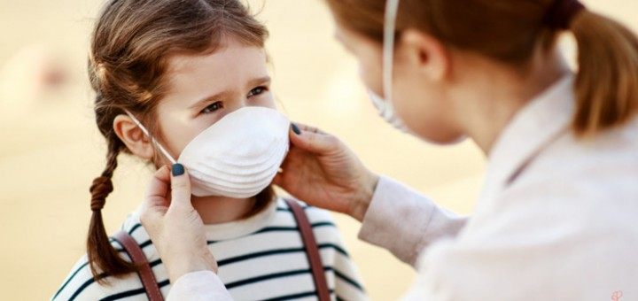 Mother putting on medical mask on daughter